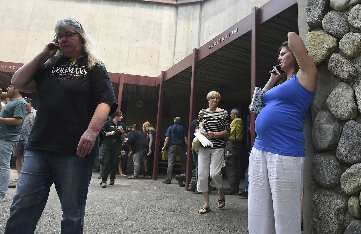 Brooke Smith, right, who lives in Yosemite Valley, talks on the phone after attending a community meeting for the latest information about the Ferguson Fire Tuesday, July 24, 2018, in Yosemite National Park, Calif. A Yosemite National Park official says at least a thousand campground and hotel reservations will be canceled after authorities decided to close Yosemite Valley to keep a growing forest fire at bay. Spokesman Scott Gediman says the valley, the heart of the visitor experience at the park, along with a windy, mountainous, 20-mile (32-kilometer) stretch of State Route 41 that is part of Yosemite will close beginning Wednesday at noon. (Eric Paul Zamora/The Fresno Bee via AP)