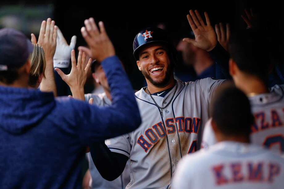 DENVER, CO - JULY 24:  George Springer #4 of the Houston Astros celebrates in the dugout after scoring on a home run by teammate Alex Bregman in the first inning against the Colorado Rockies during interleague play at Coors Field on July 24, 2018 in Denver, Colorado.  PHOTOS: What we know about Roberto Osuna, the Astros' newest reliever. Photo: Justin Edmonds, Getty Images / 2018 Getty Images