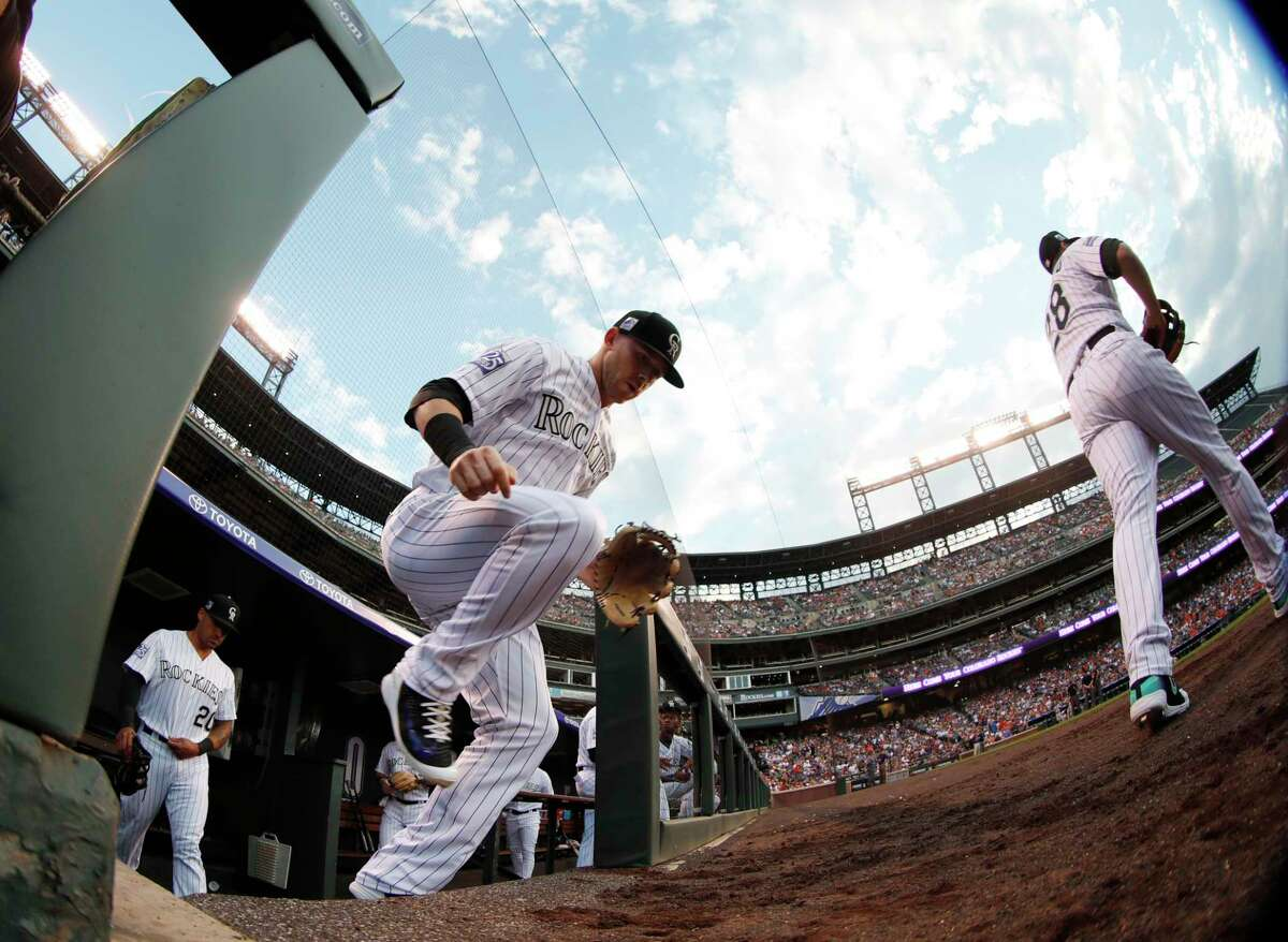 As viewed through a fisheye lens, Colorado Rockies shortstop Trevor Story takes the field for the start of the team's baseball game against hte Houston Astros on Tuesday, July 24, 2018, in Denver. (AP Photo/David Zalubowski)