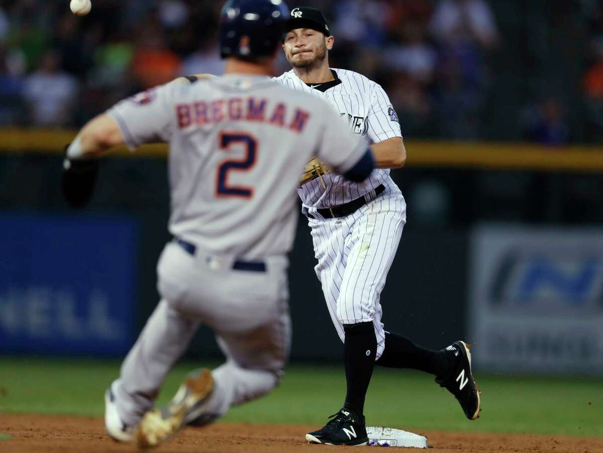 Colorado Rockies second baseman Garrett Hampson, back, forces out Houston Astros' Alex Bregman at second base on the front end of a double play hit into by Jose Altuve during the third inning of a baseball game Tuesday, July 24, 2018, in Denver. (AP Photo/David Zalubowski)