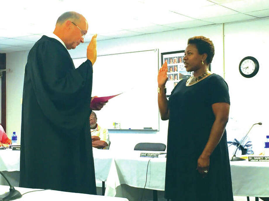 Madison County's Chief Judge David Hylla swears in the Edwardsville District 7's new board member Nekisha Omotola during the general board of education meeting Monday night. Omotola was appointed to fill the seat of William Catalano who resigned at the last board meeting. Photo:       Julia Biggs | For The Telegraph