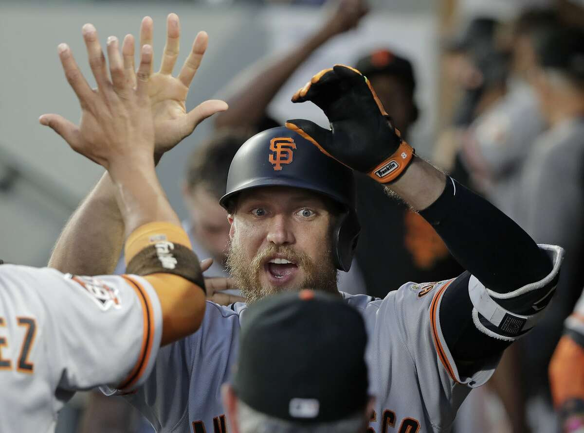 San Francisco Giants' Hunter Pence is greeted in the dugout after he hit a solo home run against the Seattle Mariners during the sixth inning of a baseball game Tuesday, July 24, 2018, in Seattle.