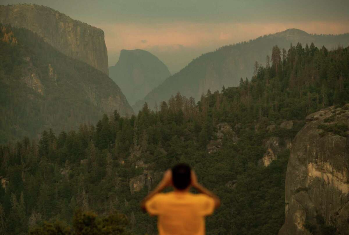 Francisco Avendano, visiting from Madrid, Spain, photographs Half Dome as smoke from the Ferguson Fire hangs over Yosemite National Park, Calif., on Tuesday, July 24, 2018. Parts of the park, including Yosemite Valley, will close Wednesday as firefighters work to contain the blaze.