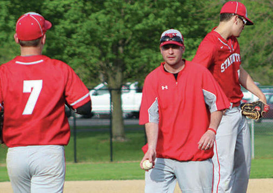 Staunton coach Kyle McBrain (center) flips the baseball to reliever Cullen McBride (7) after making a pitching change in a May 8 loss to Marquette Catholic at Hopkins Field in Alton. A 24-5 season with SCC and regional titles earn McBrain honors as 2018 Telegraph Small-Schools Baseball Coach of the Year. Photo:       Greg Shashack / Telegraph File Photo