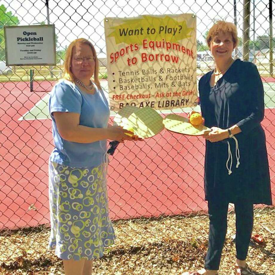 (From left) Deb Gainor, library board member, and Angela Hass, one of the organizers, add to the long list of sports equipment to borrow from the Bad Axe District Library, by recently accepting a donation of four paddles and a ball from the Bad Axe Pickleball Association. (Submitted Photo)