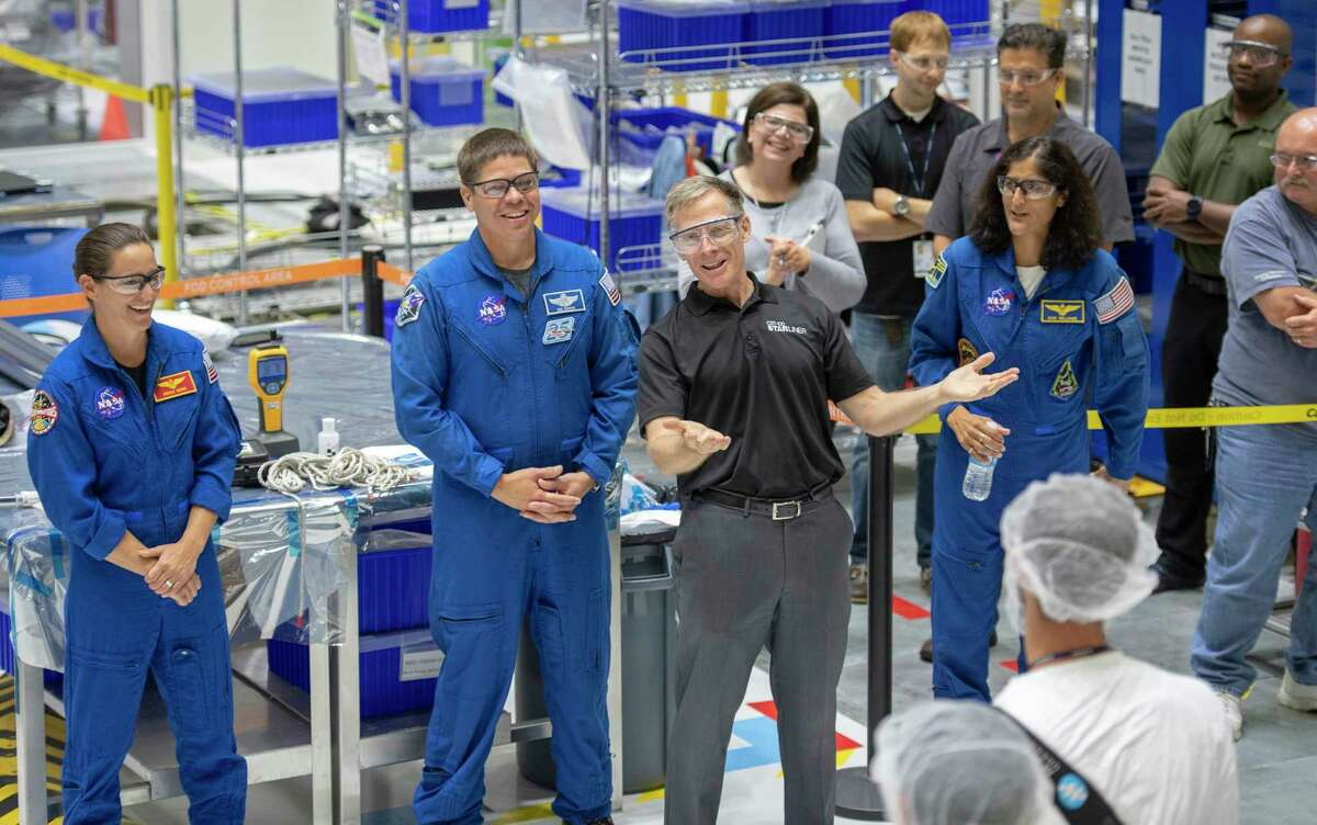 Chris Ferguson (center), Boeing director of Starliner crew and mission operations with (from left): NASA astronauts Nicole Mann, Bob Behnken and Sunita Williams, talks with Boeing employees after they assembled part of the Starliner spacecraft.