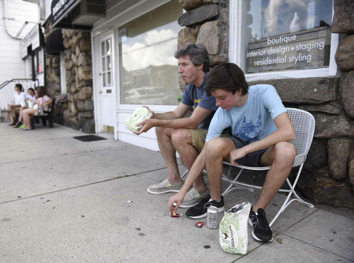Santiago and Milo Bausili, of Buenos Aires, eat outside Garden Catering in Old Greenwich, Conn. Tuesday, July 24, 2018. The beloved chicken nugget joint is adding a store in New Haven in August, joining seven other locations throughout Fairfield County and Westchester County, N.Y.