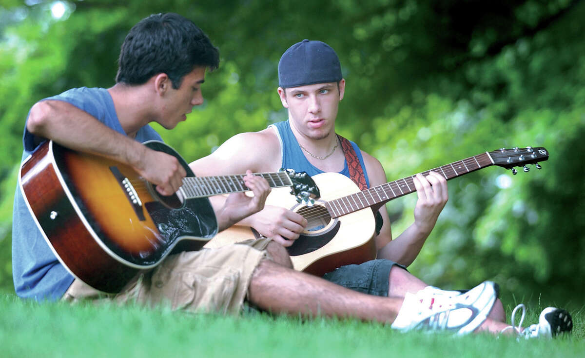 FILE: Rob Vine (right), a flimmaking student with the Center for Creative Youth at Wesleyan University, teaches his visiting friend, Jason Arisco, some chords on Foss Hill at Wesleyan. CCY is a pre-college program that runs in the summer for five weeks at Wesleyan. The students study their choice of an art form from several options, including music, dance, theater, creative writing and visial arts.