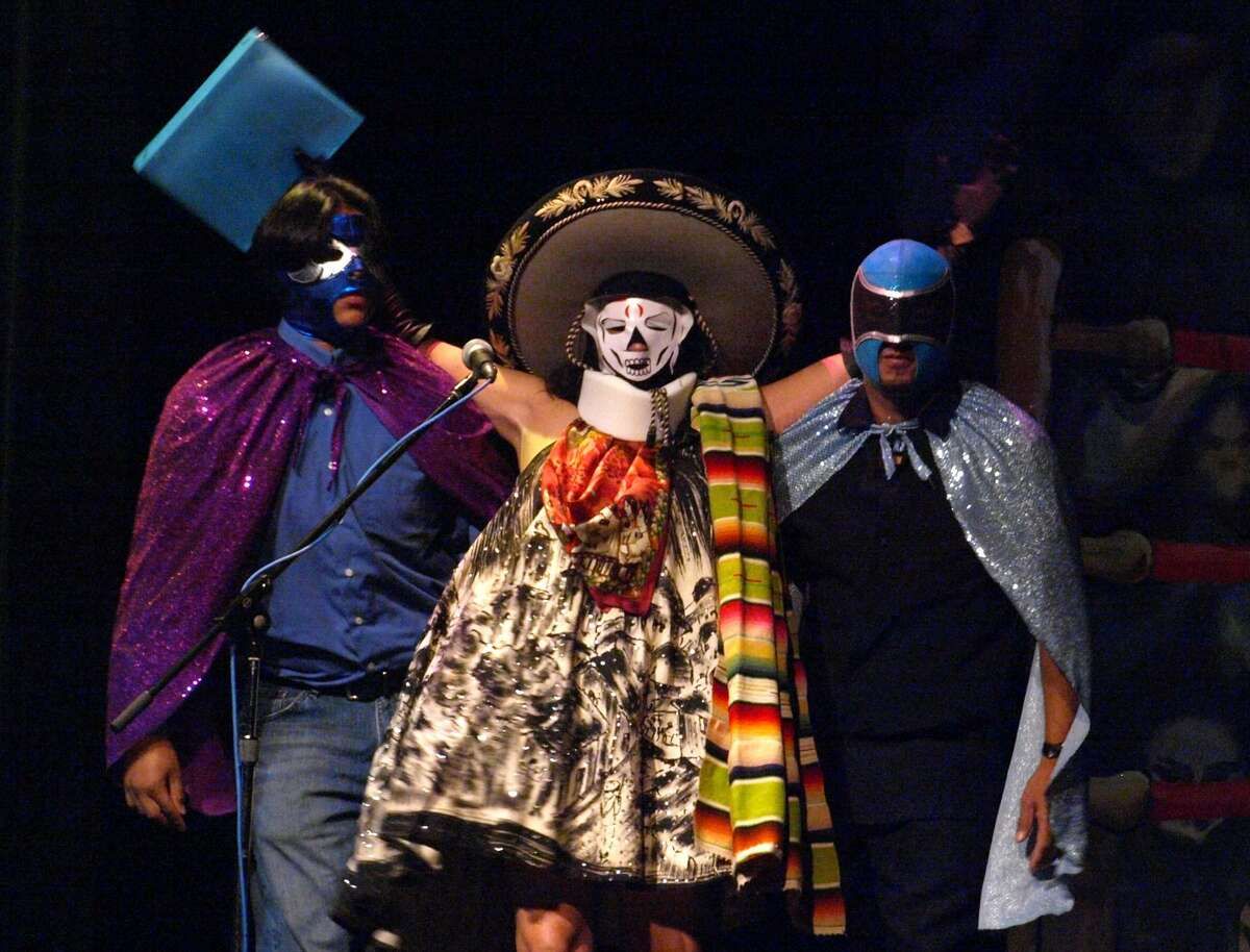 A masked Sandra Cisneros, center, arrives on stage carried by two masked
