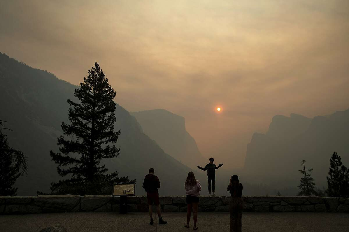 Hannah Whyatt poses for a friend's photo as smoke from the Ferguson fire fills Yosemite Valley, Wednesday, July 25, 2018, in Yosemite National Park, Calif. Campsites and lodges emptied out after disappointed tourists were ordered to leave the heart of Yosemite National Park by noon Wednesday, as firefighters battled to contain a huge wildfire just to the west that has threatened the park's forest and sent up smoke that obscured grand vistas of waterfalls and sheer granite faces. (AP Photo/Noah Berger)