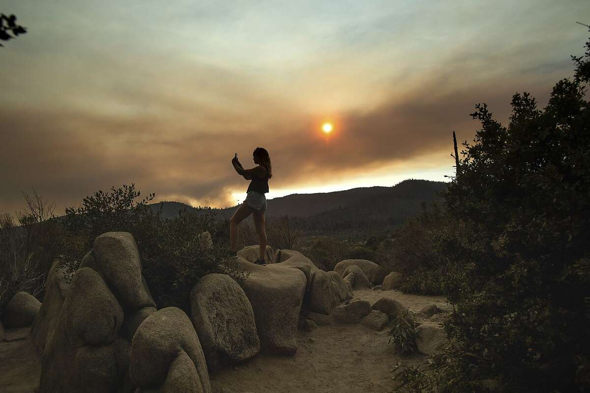 Mara Schumann photographs a plume of smoke from the Ferguson Fire in Yosemite National Park, Calif., on Tuesday, July 24, 2018. Parts of the park, including Yosemite Valley, will close Wednesday as firefighters work to stop the blaze. (AP Photo/Noah Berger)