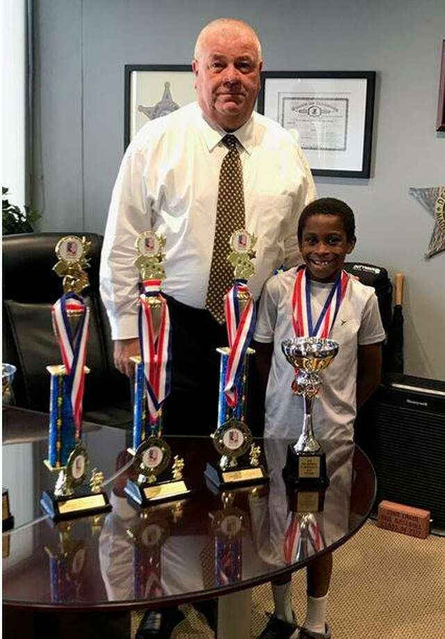 Glen Carbon resident Micah Miner, right, shows his trophies and medals from recent competitions to Madison County Sheriff John Lakin. Photo:       For The Telegraph