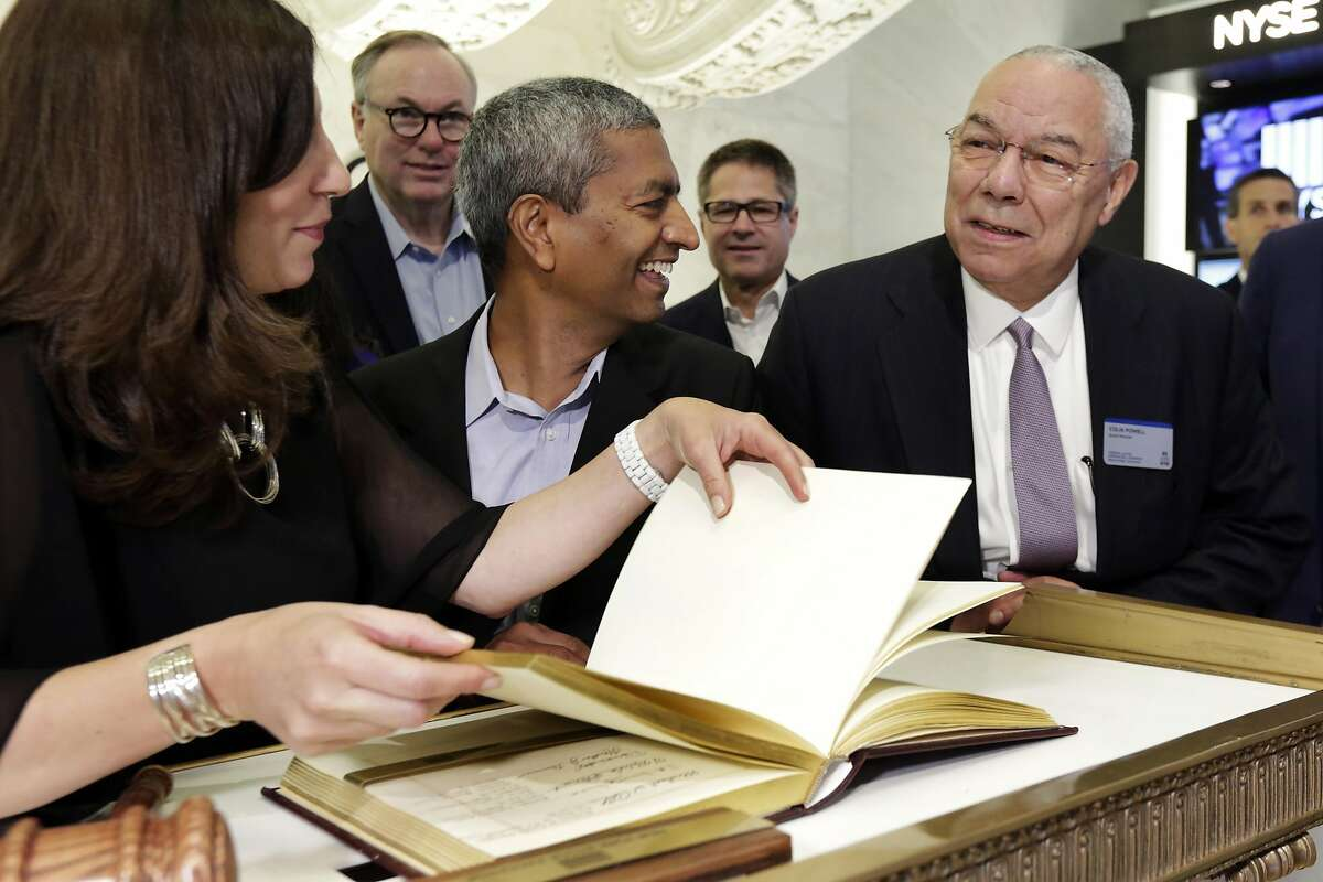 Bloom Energy Founder, President and CEO K.R. Sridhar, center accompanied by board member Colin Powell, right, prepares to sign the New York Stock Exchange guest book with NYSE President Stacey Cunningham before their IPO, Wednesday, July 25, 2018. (AP Photo/Richard Drew)