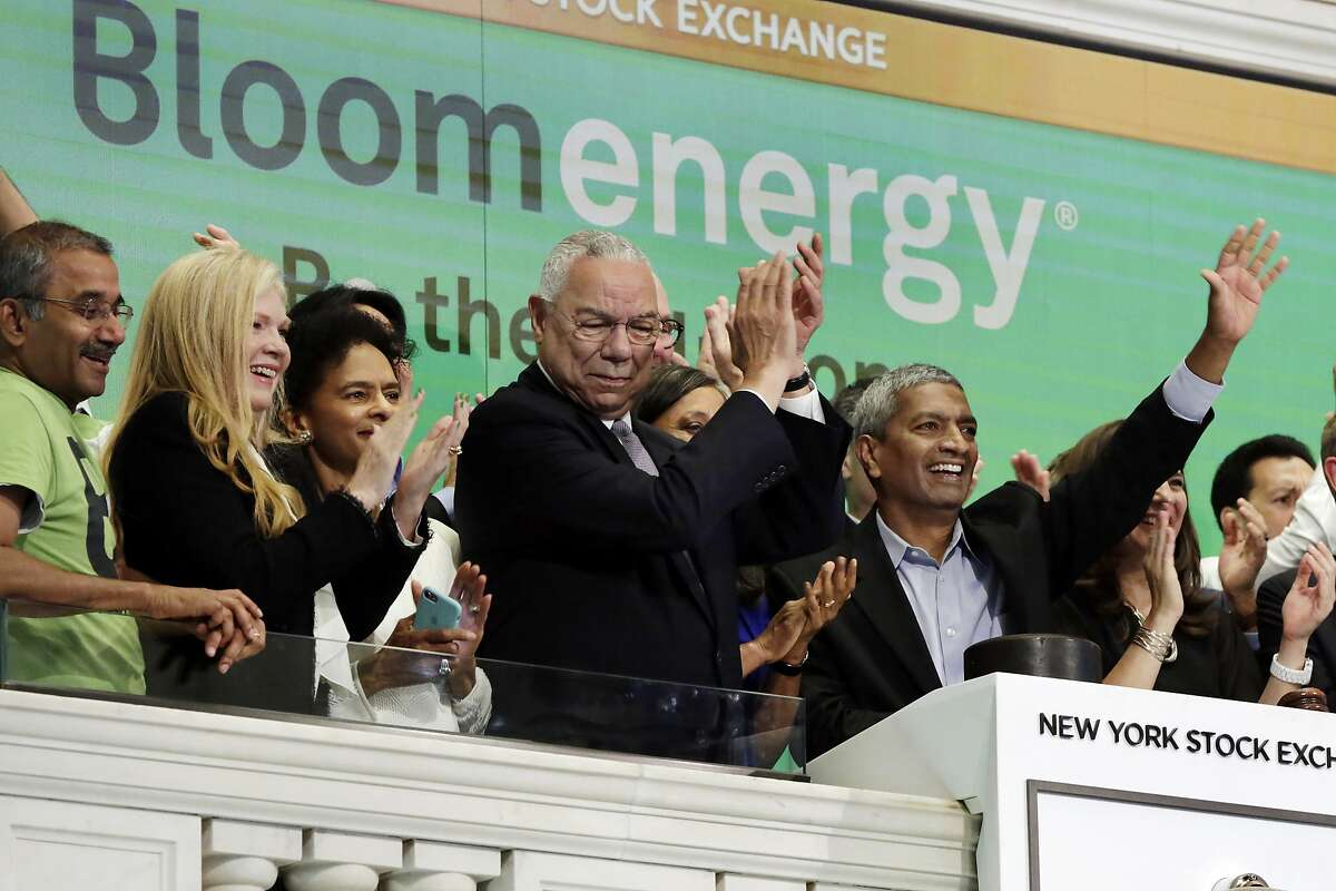 Bloom Energy Founder, President and CEO K.R. Sridhar, right, is applauded by board member Colin Powell, center, and company officials as he rings the New York Stock Exchange opening bell, Wednesday, July 25, 2018, to mark their IPO. (AP Photo/Richard Drew)