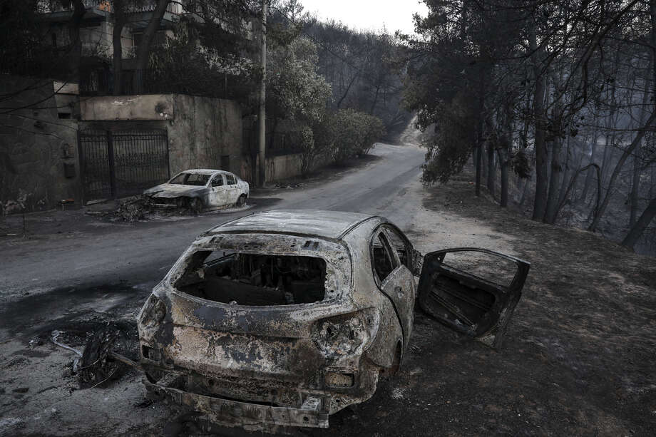Burnt automobile shells line the streets following a wildfire at Neos Voutzas village, east of Athens, Greece, on July 25, 2018. Photo: Bloomberg Photo By Yorgos Karahalis. / © 2018 Bloomberg Finance LP