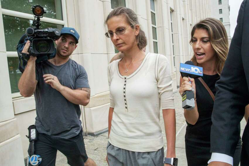 Clare Bronfman, center, arrives at federal court, Wednesday, July 25, 2018, in the Brooklyn borough of New York. Bronfman, an heiress to the Seagram's liquor fortune and three other people were arrested on Tuesday in connection with the investigation of a self-improvement organization accused of branding some of its female followers and forcing them into unwanted sex.