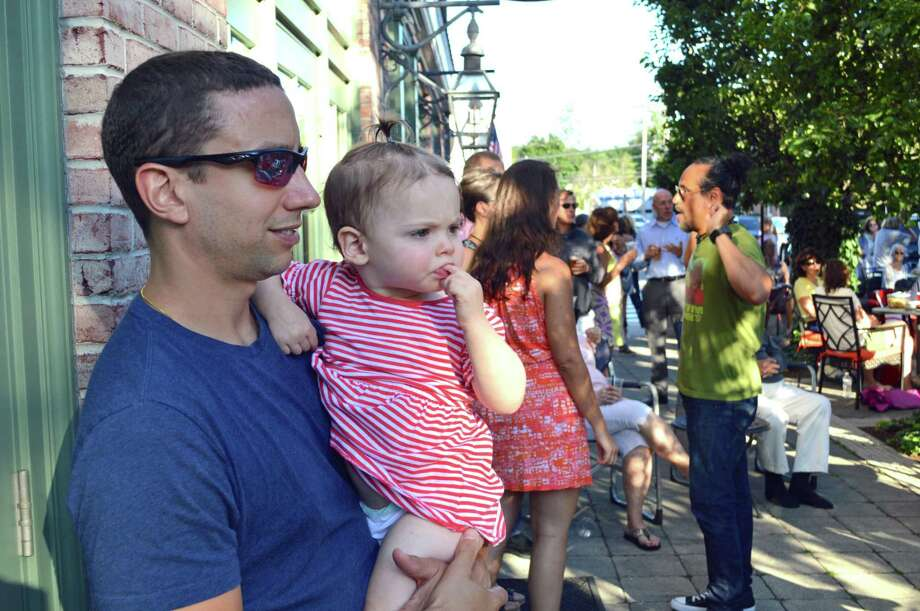 Above left, Matt Ward, of Darien, and his daughter, Annie, 18 months, listen to a song. Photo: Jarret Liotta / For Hearst Connecticut Media / Darien News Freelance