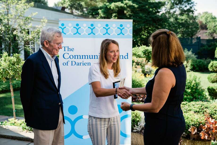 Community Fund incoming board president Frank Huck and Community Fund Director of Development Laurie Orem award a check to Marissa Mangone, director of business development for the Child Guidance Center of Mid-Fairfield County. Photo: Contributed Photo / Calderwood Digital