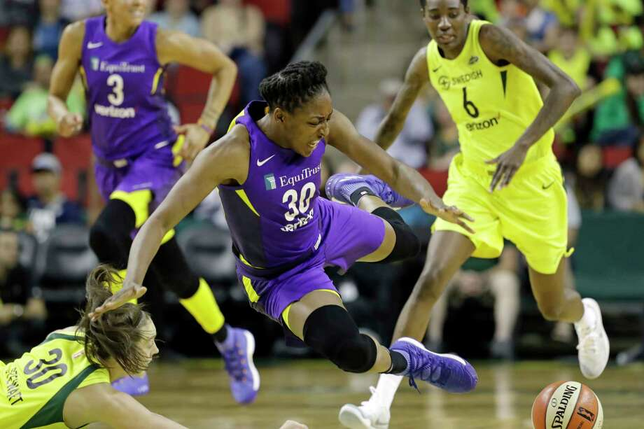 Los Angeles Sparks' Nneka Ogwumike, center, tumbles after being fouled by Seattle Storm's Breanna Stewart, left, in the first half of a WNBA basketball game Tuesday, July 10, 2018, in Seattle. (AP Photo/Elaine Thompson) Photo: Elaine Thompson, Associated Press / Copyright 2018 The Associated Press. All rights reserved