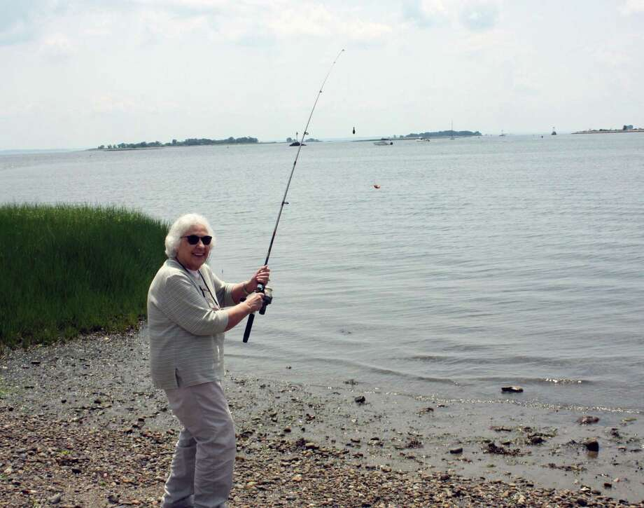 Waveny LifeCare Network Adult Day Program participant, Eleanor, casts a line off the shore of Calf Pasture Beach during a recent fishing trip with fellow program participants and assisted living residents from The Village. Photo: Contributed Photo
