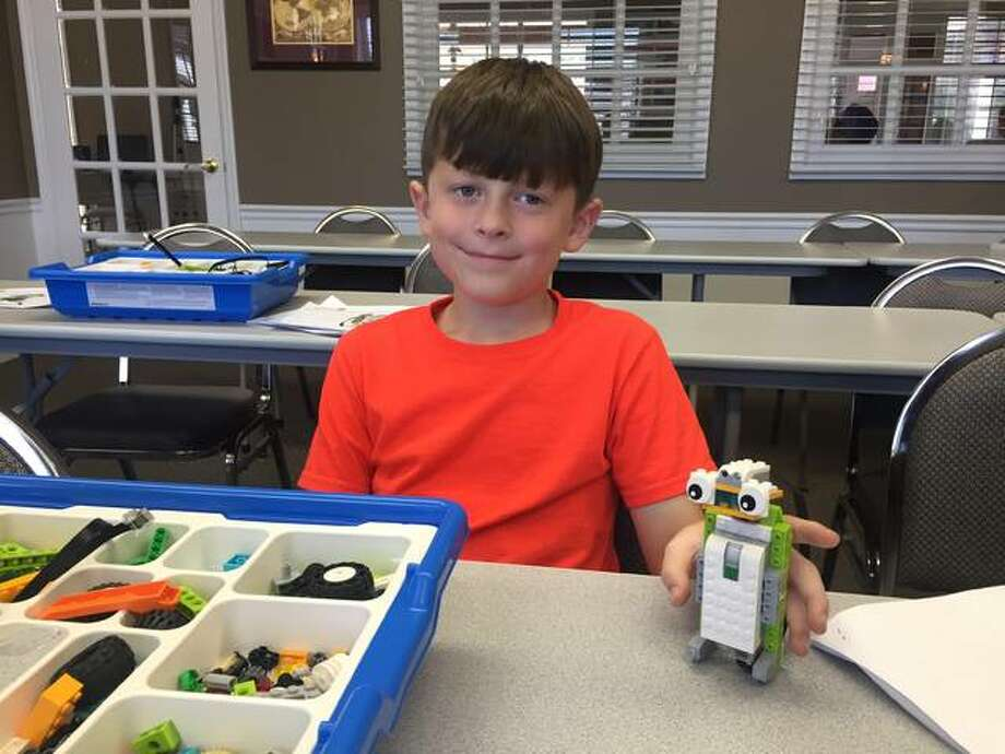 Gregory Sams shows off all of his hard work after completing a Spy Robot. Photo:       For The Telegraph