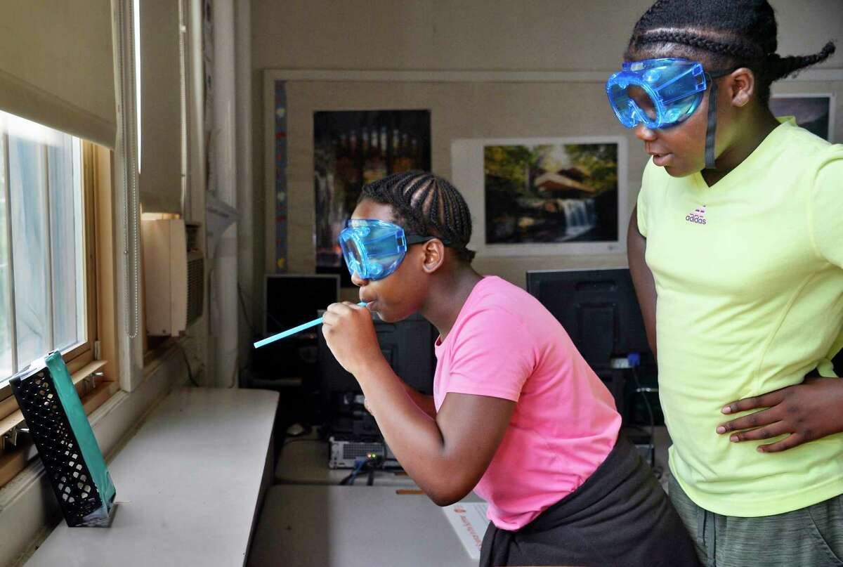 Zhakiyah Smith, left, and Kelises Myers conduct an experiment during the GSK Science in the Summer program at Pleasant Valley Elementary School Tuesday July 24, 2018 in Schenectady, NY. (John Carl D'Annibale/Times Union)