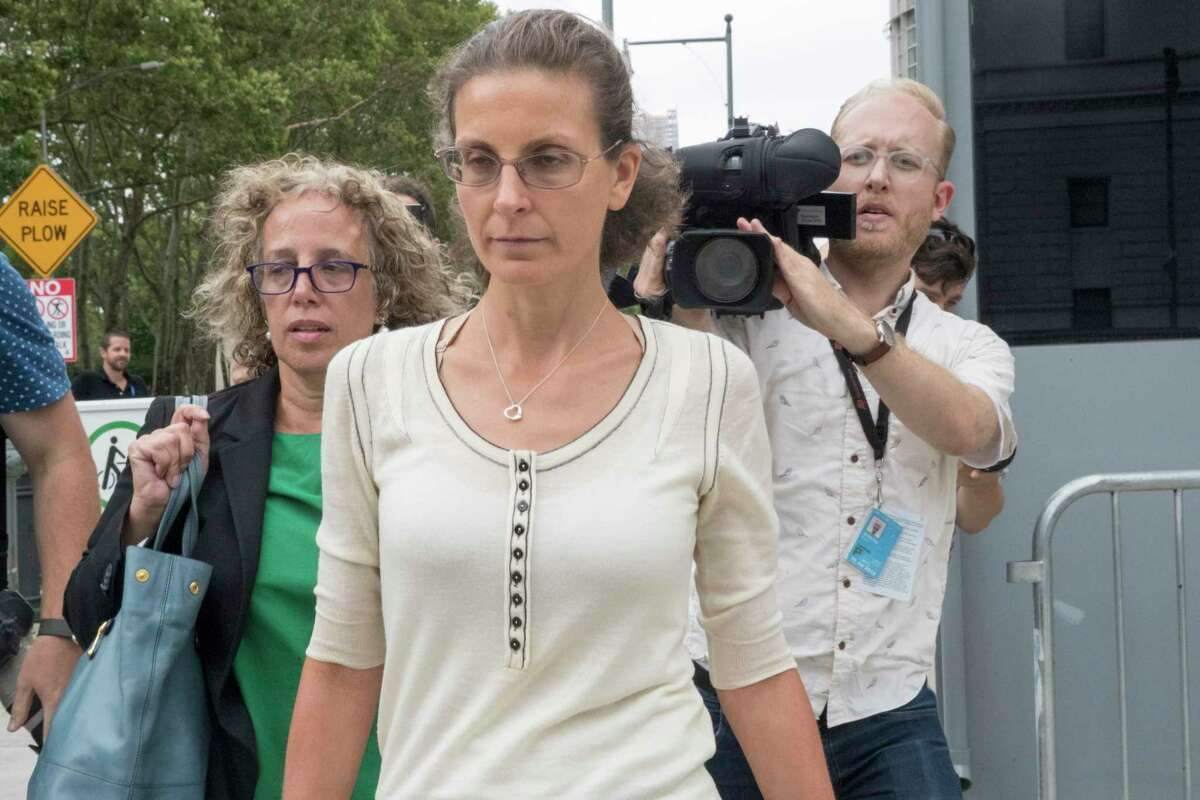 Clare Bronfman, center, leaves Federal court with her attorney Susan Necheles, left, Wednesday, July 25, 2018, in the Brooklyn borough of New York.