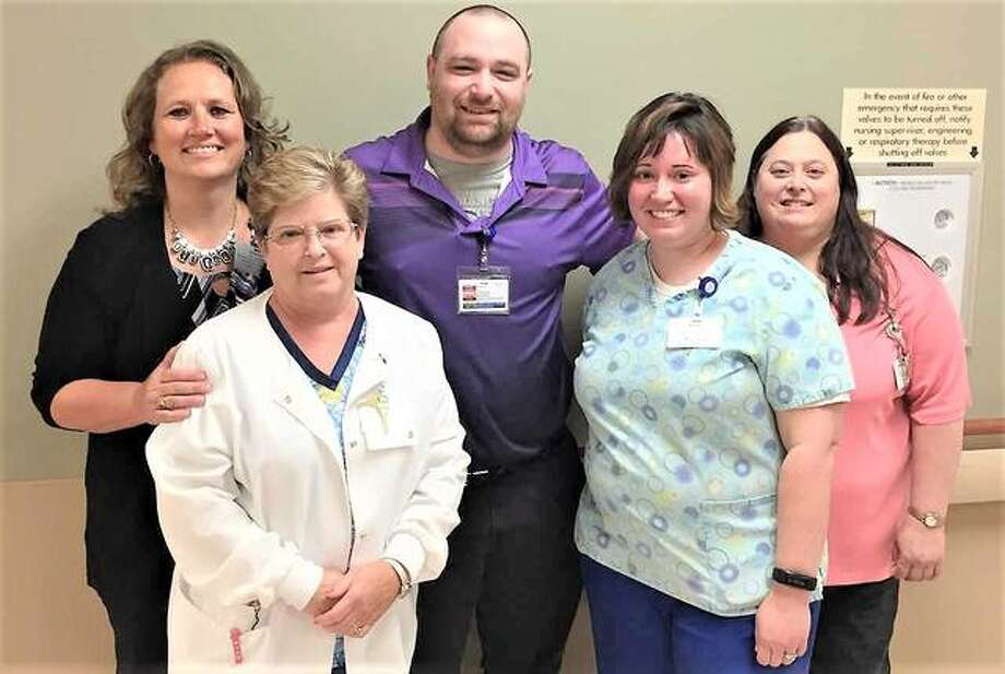 "Jeremy Clements of Medical Imaging, center, surrounded by some of his co-workers, is Alton Memorial Hospital's Employee of the Month for July. No fewer than seven of his co-workers nominated Clements for the honor, with many of them referring to his expertise in Epic, the electronic health records system that went live last December. Their comments include: ""Jeremy was given the task of our Epic Super User, attended about 10 classes, or more, and dove head-first to help each of us in the front desk position learn how Epic worked. Once we went live with Epic, Jeremy worked 13-hour days for a minimum of two weeks, never once complaining about this. He was always being pulled to answer questions from all areas in the department to help avoid major issues, without sacrificing patient care. I started calling him 'Mr. Epic' because he is so knowledgeable. He never seems put out to help and does help with a smile."" Photo:       For The Telegraph"