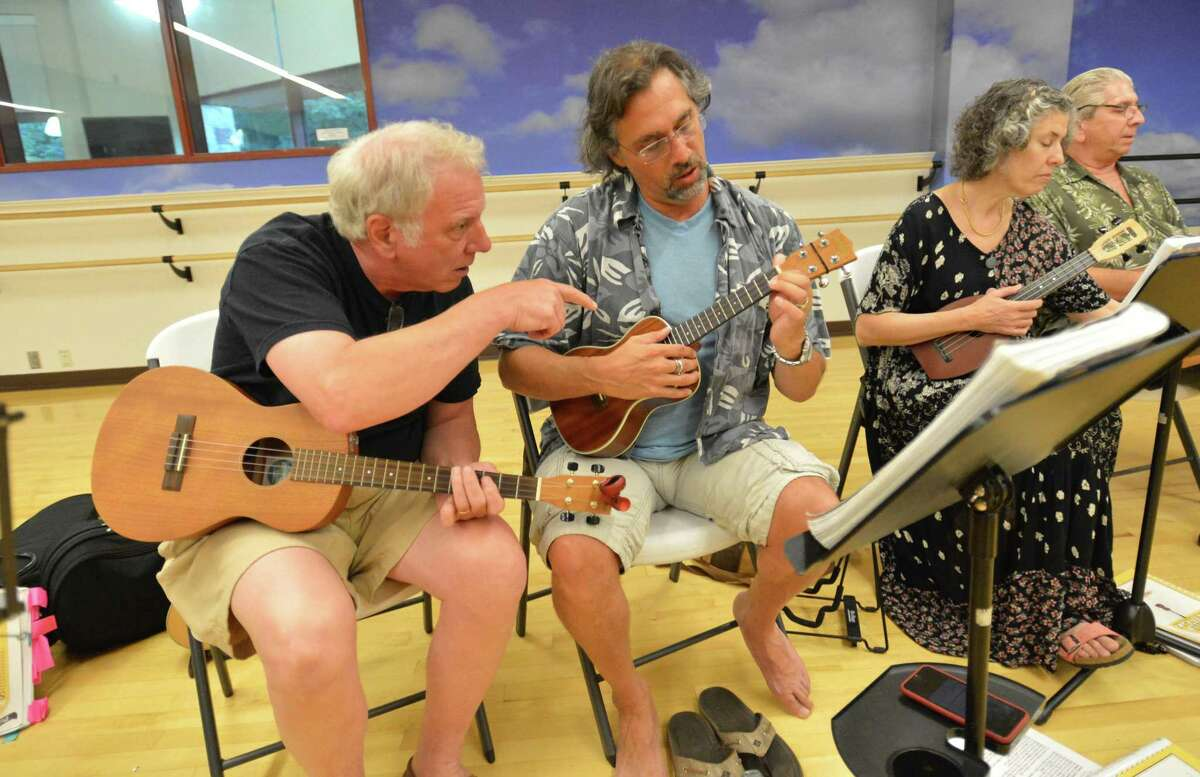 Organizer Norwalk's Steve Folano helps Glenn Hayes with the correct chord during the weekly ukulele class at the Westport YMCA on Tuesday.
