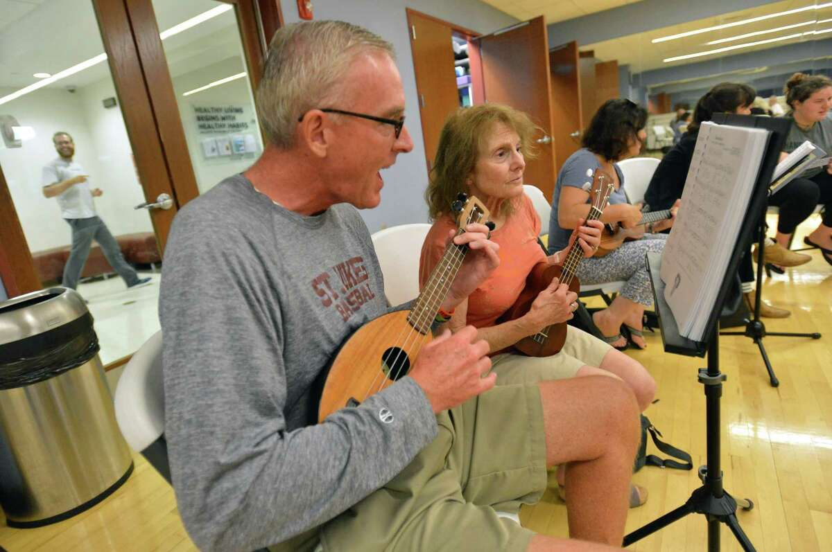 Westport's Tom Whelan and Janet Horowitz play along during the weekly ukulele class at the Westport YMCA on Tuesday.