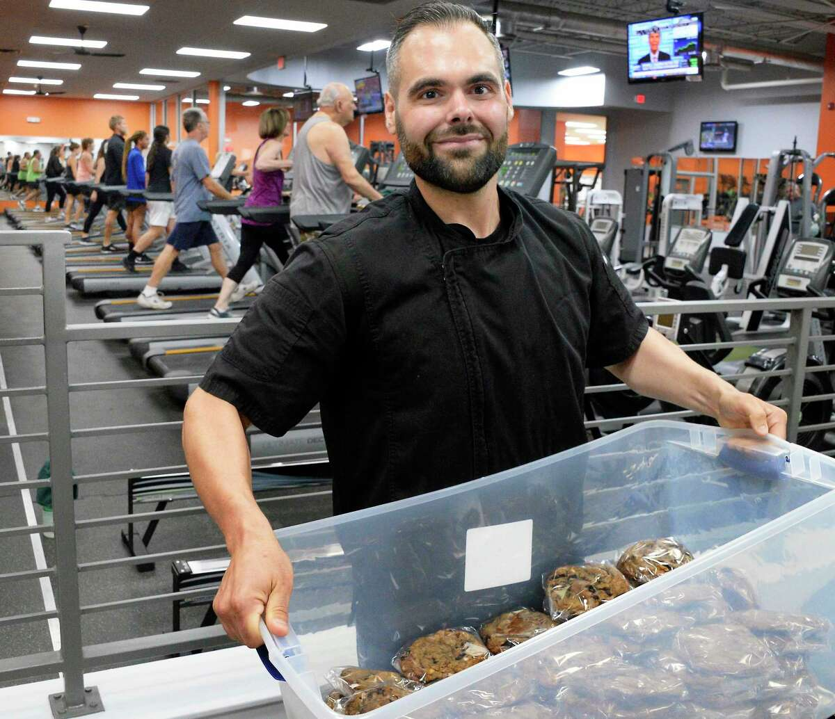 """James Basile, the Anabolic Baker, carries in a bin of """"heathy"""" sweets for sale to fitness buffs inside ABC Fitness Tuesday July 17, 2018 in Colonie, NY. (John Carl D'Annibale/Times Union)"""
