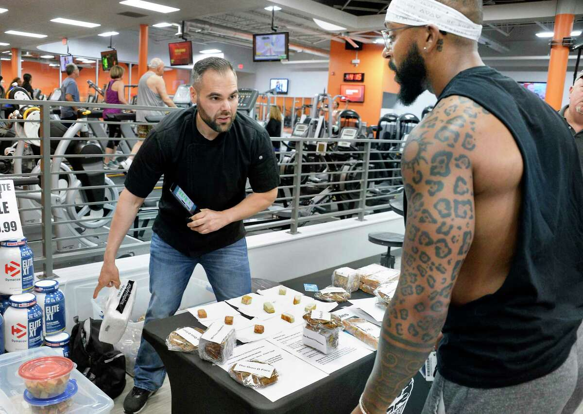 """James Basile, the Anabolic Baker, left, offers a variety of his """"heathy"""" sweets to Robbie Gardner of Troy inside ABC Fitness Tuesday July 17, 2018 in Colonie, NY. (John Carl D'Annibale/Times Union)"""