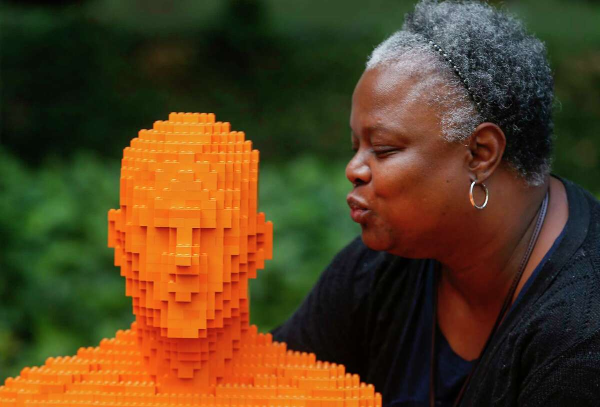 Tammy Pruitt gets prepared to give one of a Nathan Sawaya's Park People installation a kiss Wednesday, July 25, 2018, in Houston.