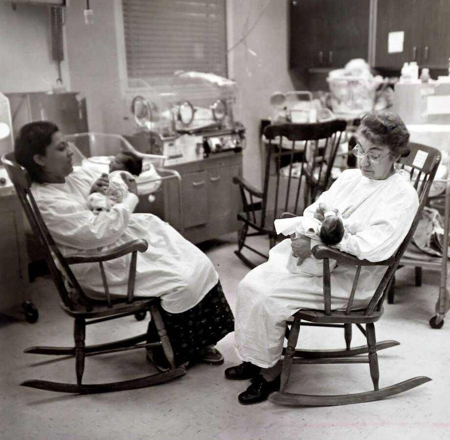 Foster Grandparent Program participant Mary Gervasio, right, feeds a baby in the Newborn Intensive Care Unit at Yale-New Haven Hospital in 1981. Photo: Yale New Haven Hospital Archives / New Haven Register