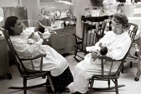 Foster Grandparent Program participant Mary Gervasio, right, feeds a baby in the Newborn Intensive Care Unit at Yale-New Haven Hospital in 1981.