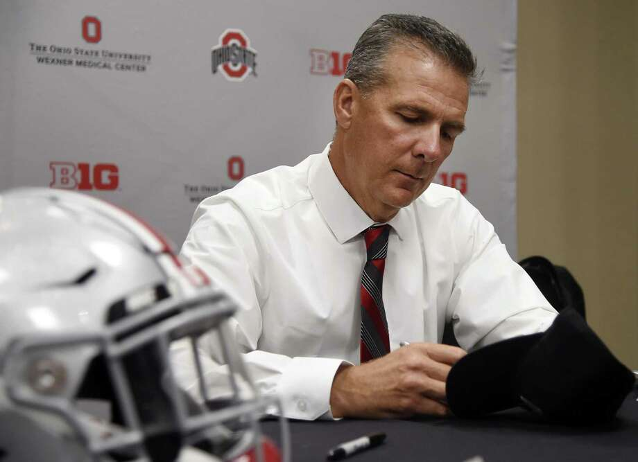Ohio State head coach Urban Meyer autographs a hat at the Big Ten Conference NCAA college football media days in Chicago, Tuesday, July 24, 2018. (AP Photo/Annie Rice) Photo: Annie Rice, STF / Associated Press / Copyright 2018 The Associated Press. All rights reserved.