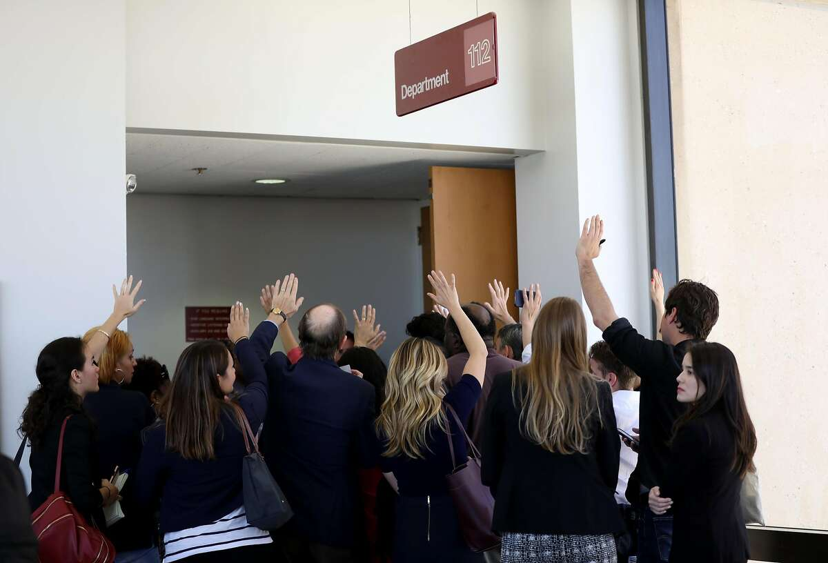 Members of the media raise their hands as they vie to grab one of the few seats available inside a courtroom to witness the arraignment of John Lee Cowell at Wiley W. Manuel Courthouse in Oakland, Cali. on Wednesday, July 25, 2018. Cowell, 27, is accused of a double stabbing, which killed Nia Wilson, 18, and injured her older sister, Lahtifa Wilson, 26, at the MacArthur BART station on Sunday evening.