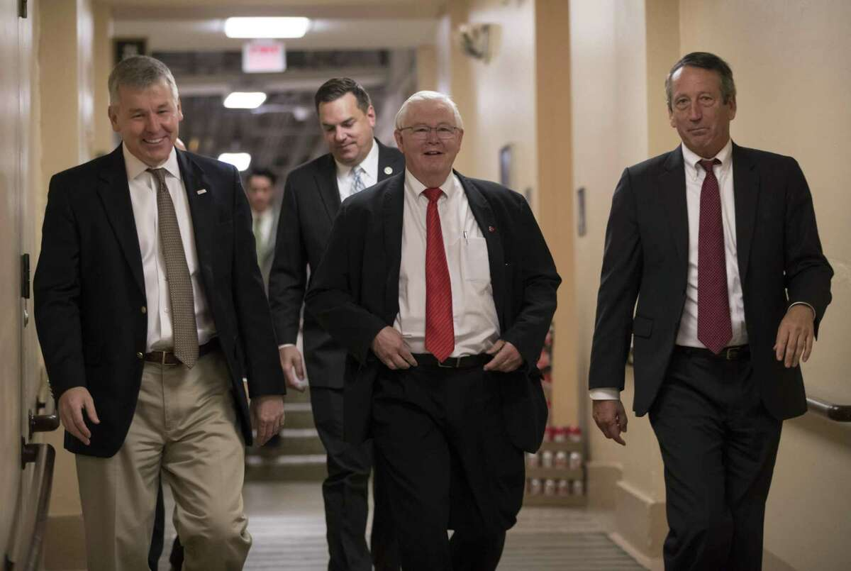 """In this Dec. 5, 2017, photo, House Republicans, from left, Rep. Rob Woodall, R-Ga., Rep. Richard Hudson, R-N.C., Rep. Joe Barton, R-Texas, and Rep. Mark Sanford, R-S.C., arrive for a closed-door strategy session on Capitol Hill in Washington. Sounding a discordant note among the positive talk on the tax bill, a number of Republicans are delivering a blunt assessment, casting the bill as a boost to big corporations and the wealthy instead of the middle class. """"Fundamentally if you look at the bulk of the bill, two-thirds of it, it's tied on the business side,?"""" Sanford said Tuesday as leaders in the House and Senate hailed their respective measures as an advantage for working Americans. (AP Photo/J. Scott Applewhite)"""