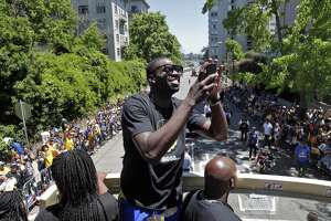 Draymond Green takes a photo of fans during the Golden State Warriors NBA Championship parade in Oakland, Calif., on Tuesday, June 12, 2018.