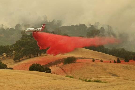 A plane dumps retardant near a house as the County Fire burns west of Esparto on Monday, July 2, 2018.