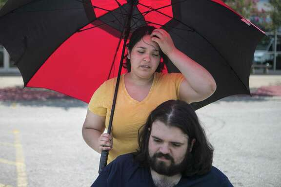 Abril Cardenas recounts her experience during the fire at Iconic Village apartments in San Marcos while standing behind her fiance Benjamin Muñoz outside the San Marcos Activity Center on July 25, 2018. He proposed marriage to her in the emergency room July 20.