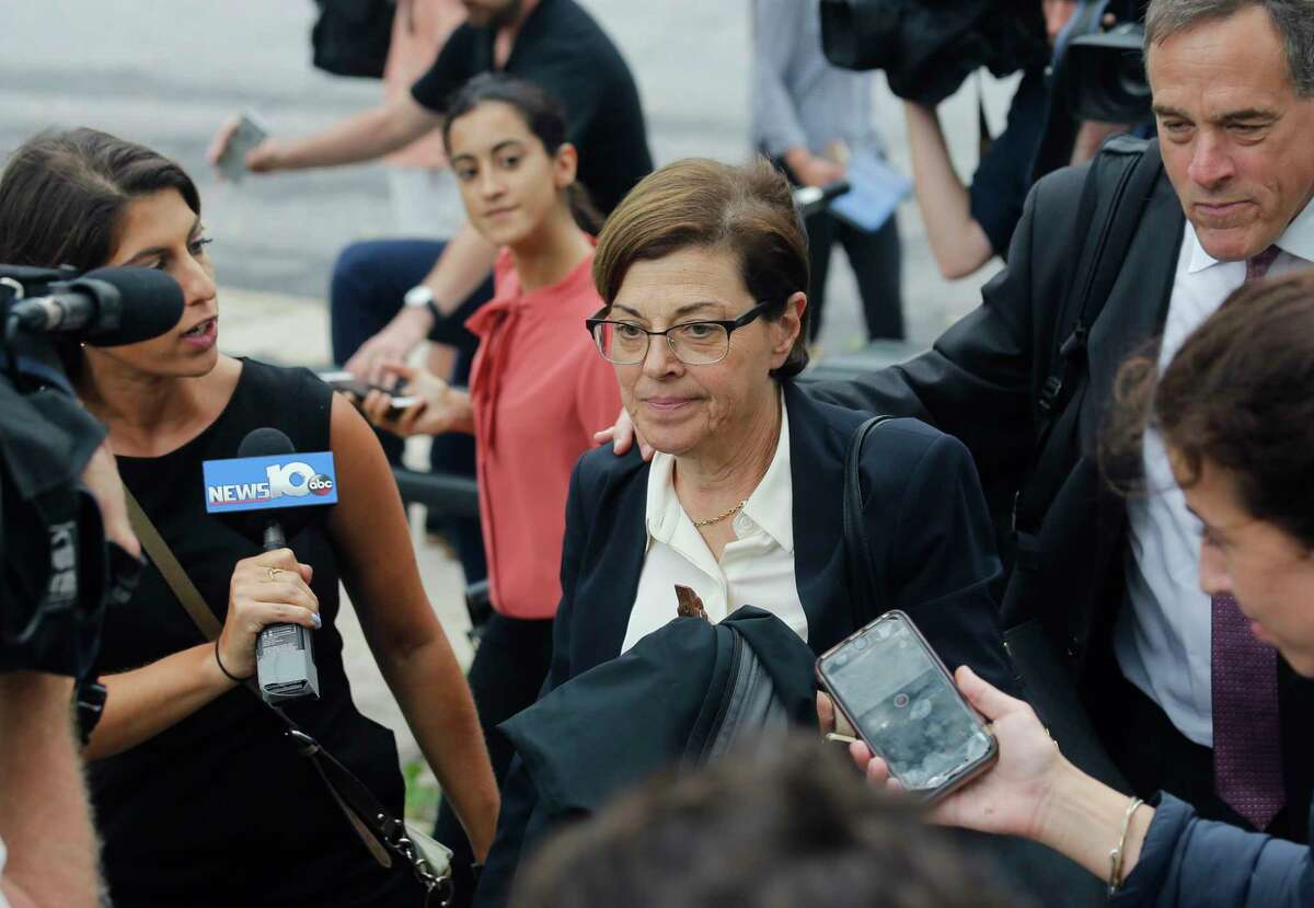Nancy Salzman, center, a defendant in a case against an upstate New York group called NXIVM, accused of branding some of its female followers and forcing them into unwanted sex, leaves federal court in Brooklyn, Wednesday July 25, 2018, in New York. (AP Photo/Bebeto Matthews)