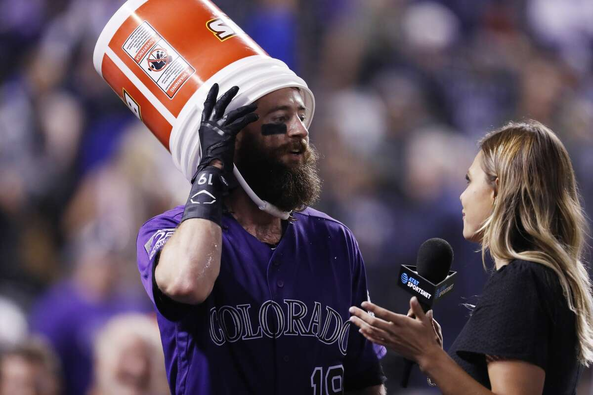 Colorado Rockies' Charlie Blackmon, left, wears a bucket after sunflower seeds were dumped on him by a teammate to mark Blackmon's walk-off solo home run against the Houston Astros in a baseball game Wednesday, July 25, 2018, in Denver. The Rockies won 3-2. On-field television reporter Taylor McGregor is at right. (AP Photo/David Zalubowski)