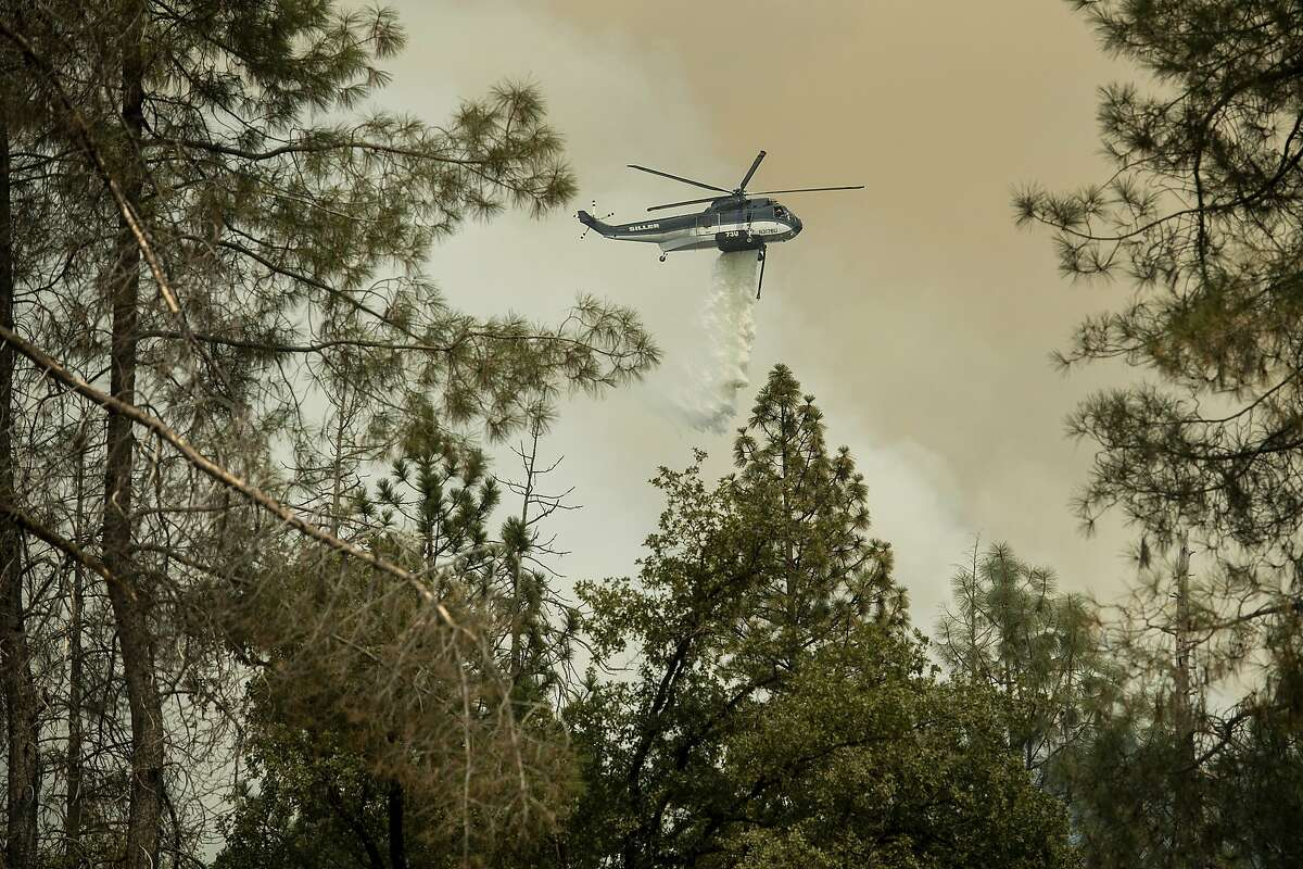 A helicopter drops water to stop the Ferguson Fire from reaching homes in the Darrah community of unincorporated Mariposa County, Calif., Wednesday, July 25, 2018. (AP Photo/Noah Berger)