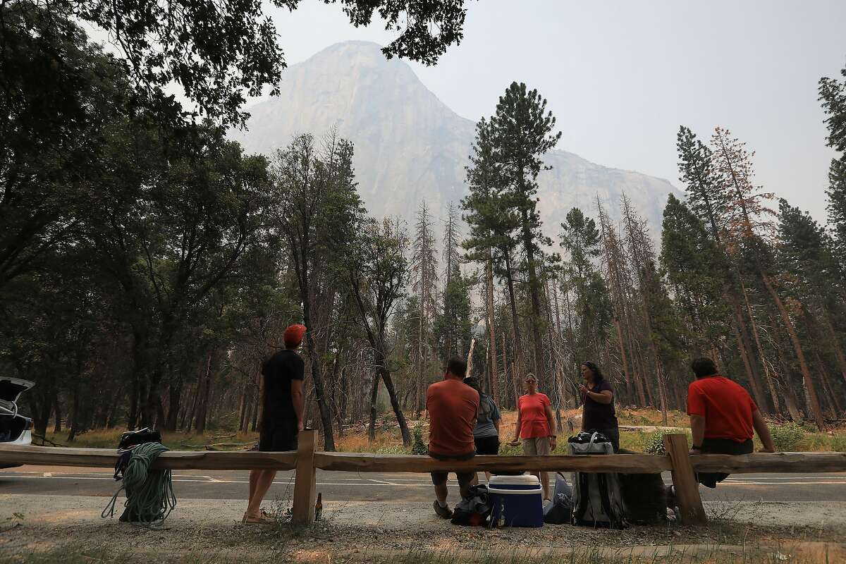 Climbers from a group that had rappelled down El Capitan pack up after rangers asked them to leave Yosemite National Park in California due to the nearby fire, July 25, 2018. Thousands of tourists were evacuated on Wednesday as one of the country�s most iconic natural preserves was blanketed with thick smoke from a 38,000-acre fire that has burned for nearly two weeks. (Jim Wilson/The New York Times)