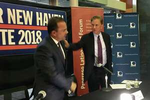 Bridgeport Mayor Joe Ganim, left, and Ned Lamont of Greenwich share a moment after a raucous debate at Albertus Magnus College in New Haven Wednesday night.