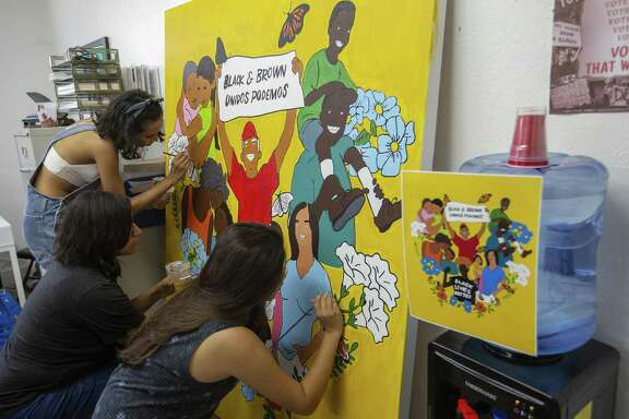Volunteer Kimberly Coronado, 22, artist and volunteer Jocelyn Riojas and volunteer Adrienne Sanchez, 20, helps paint a mural at the Jolt Texas office on July 24, 2018 in Austin, Texas.