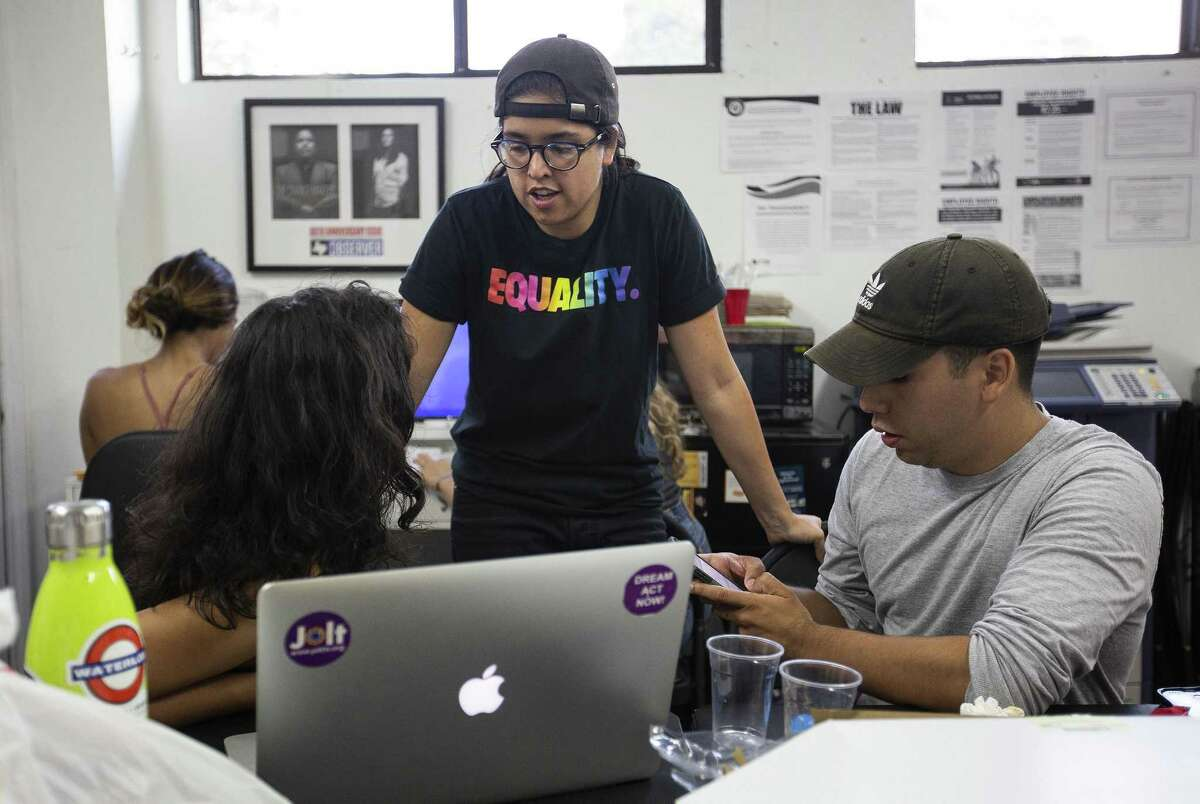 Lead organizer Tess Ortega, (center) chats with youth organizer Daniela Rojas, 23, and volunteer Jason Choto, 26, as they work on translating some text during volunteer hours at the Jolt Texas office on July 24, 2018 in Austin, Texas.