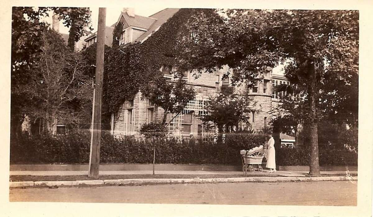 A nanny walks a baby in a carriage in front of the Maverick Carter House in this historic photo from the early 1920s.