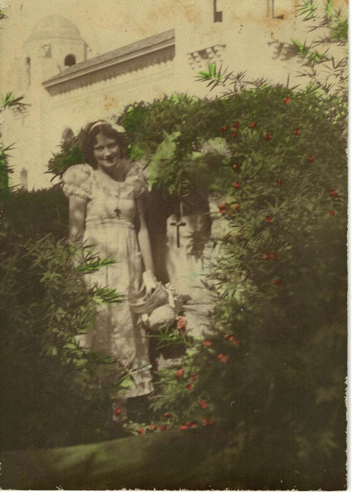 Aline B. Carter in her backyard with the Municipal Auditorium in the background in the early 1930s.